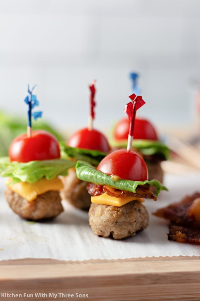 cheeseburger bites on parchment paper with red and blue toothpicks