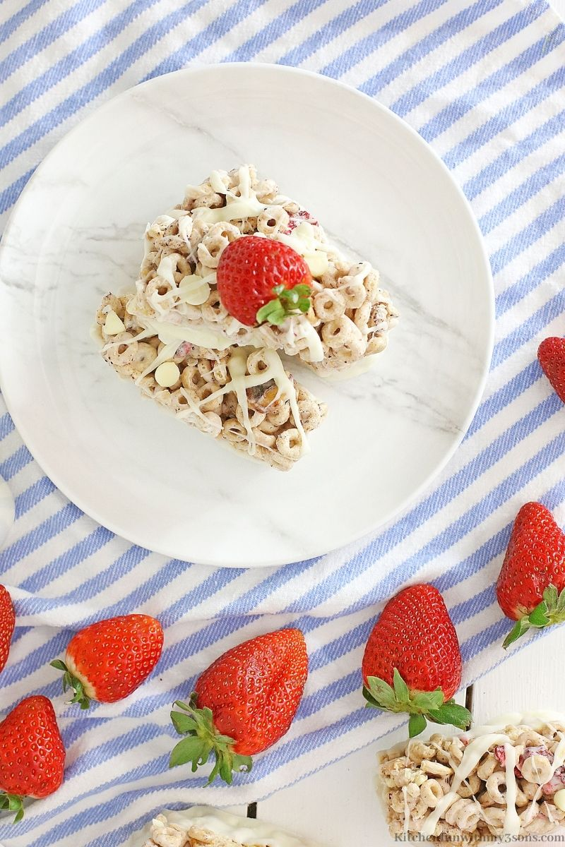 A plate with one of the Berries and Cream Cereal Bars surrounded by fresh strawberries.