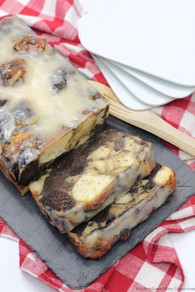Bourbon Donut Bread Pudding with a wooden spoon and extra plates.