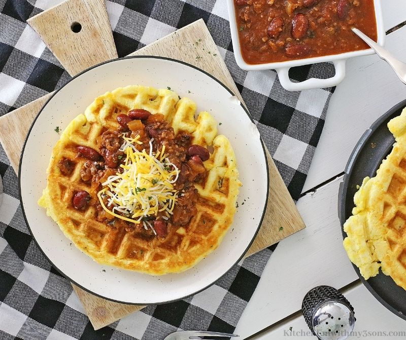 The chili on a waffle on a serving plate.