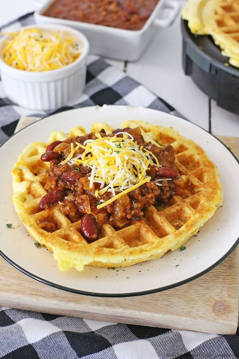 Cheesy Cornbread Waffles with Chili on a serving plate on a wooden board.