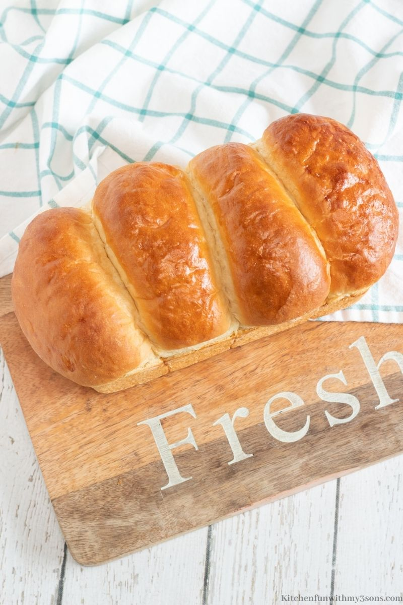 The milk bread on a wooden board with the word 'Fresh' in white lettering.