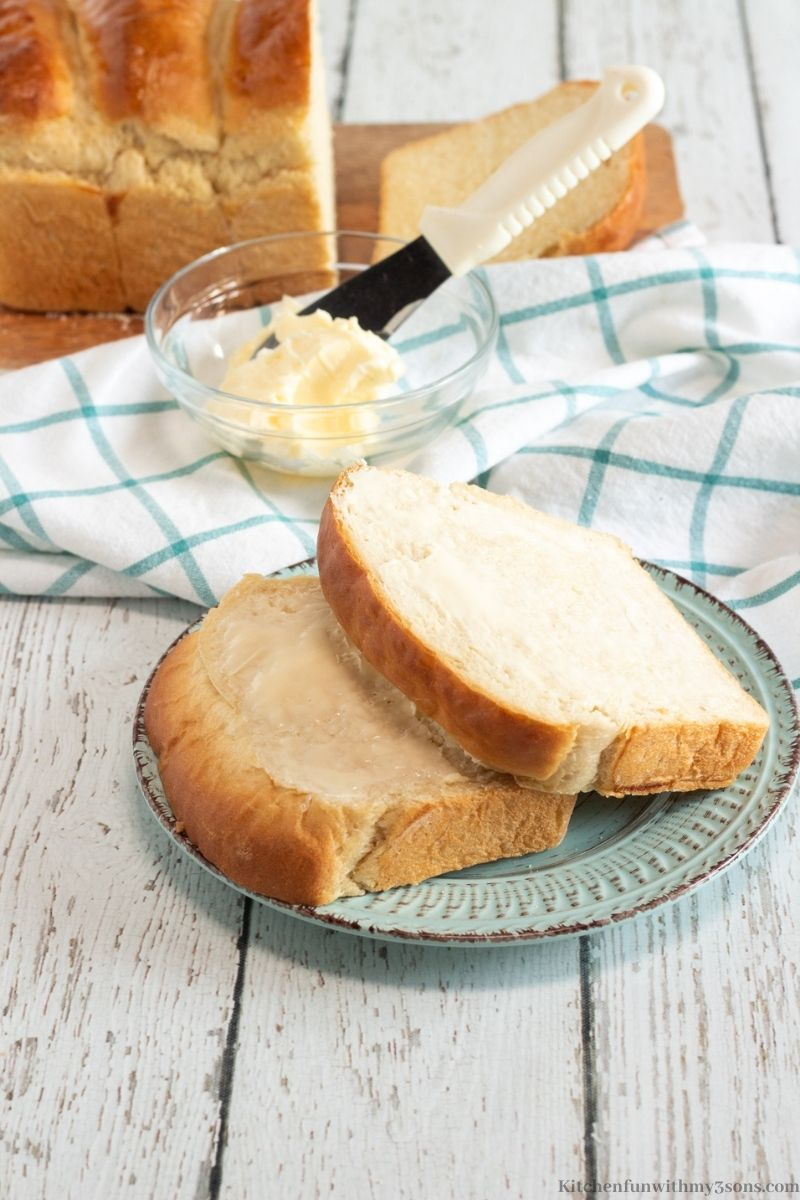 The milk bread on a small blue serving plate with butter spread evenly on one side of it.