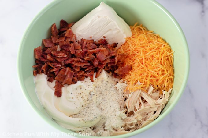 cream cheese, bacon, ranch dressing, sour cream, cheddar cheese, and shredded chicken in a mint green bowl