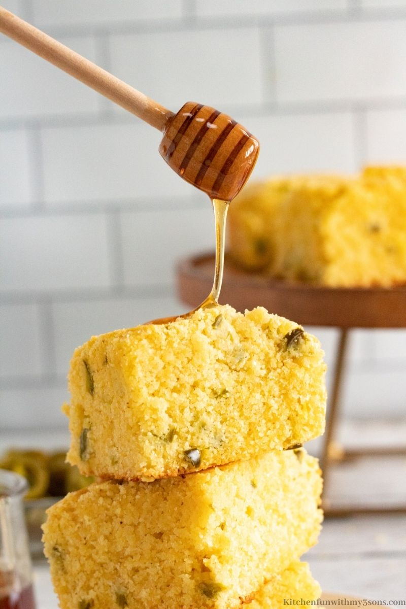 Honey being added to the top of stacked cornbread.