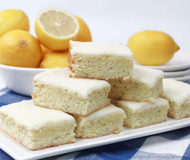 Lemon Poppy Seed Bars on a white serving plate.