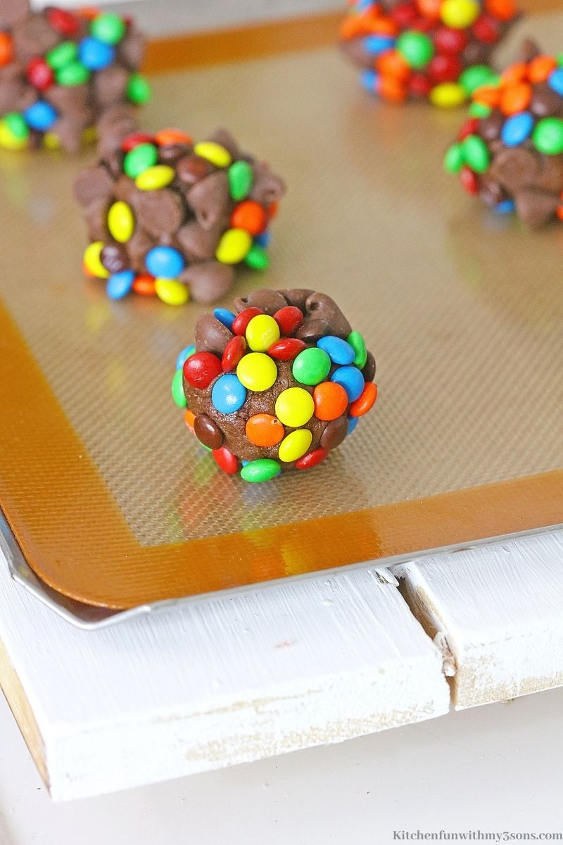 The M&M's and chocolate chips pressed into the cookie dough on the silicone line pan.