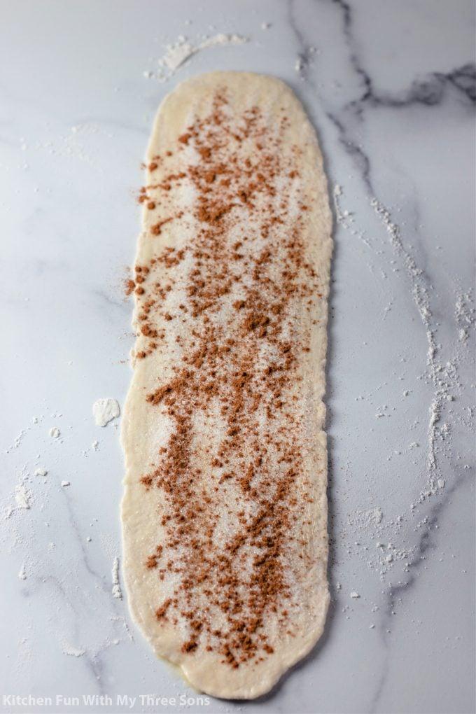 sprinkling sugar and cinnamon over the dough