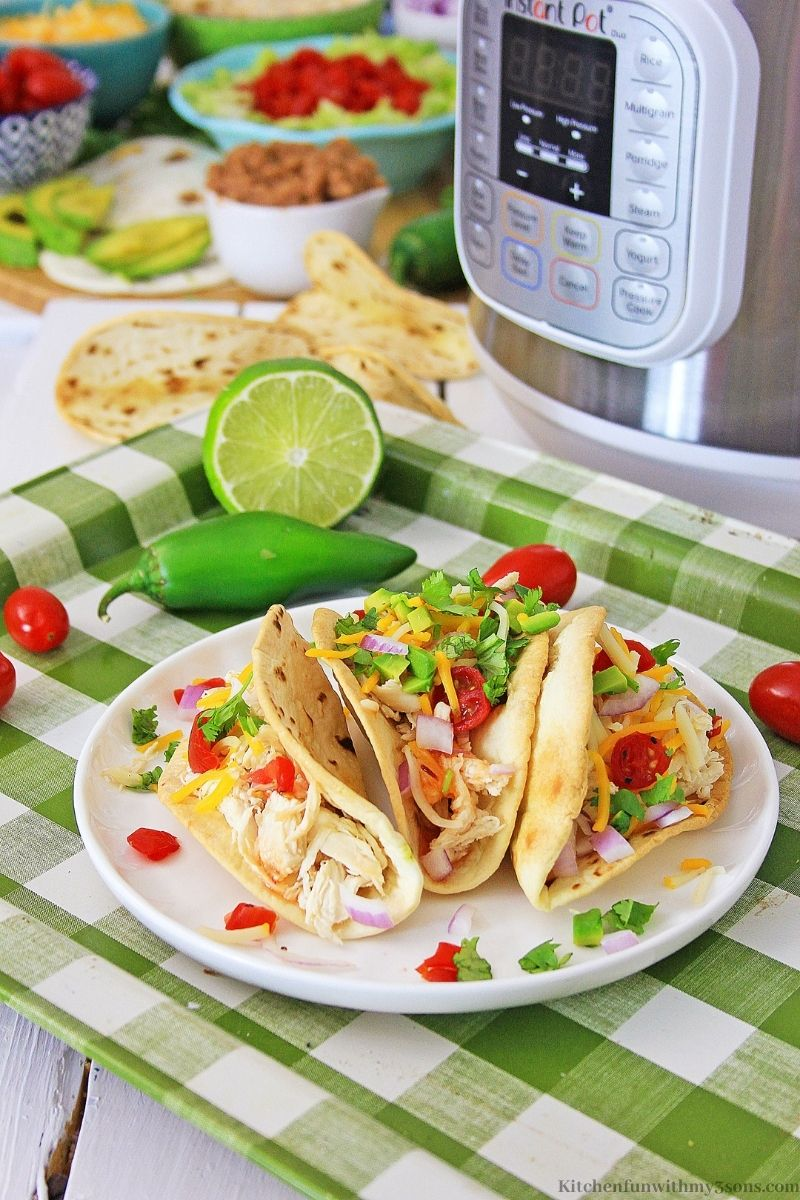 The tacos on a white and green checkered sheet pan.