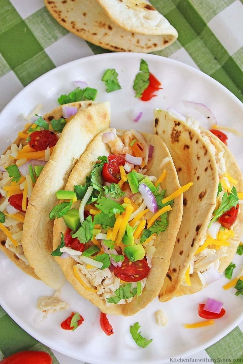 Three of the Sweet Chili Lime Instant Pot Chicken Tacos on a plate garnished with cilantro.
