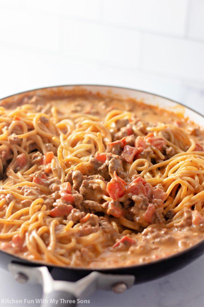 stirring the spaghetti into the sauce