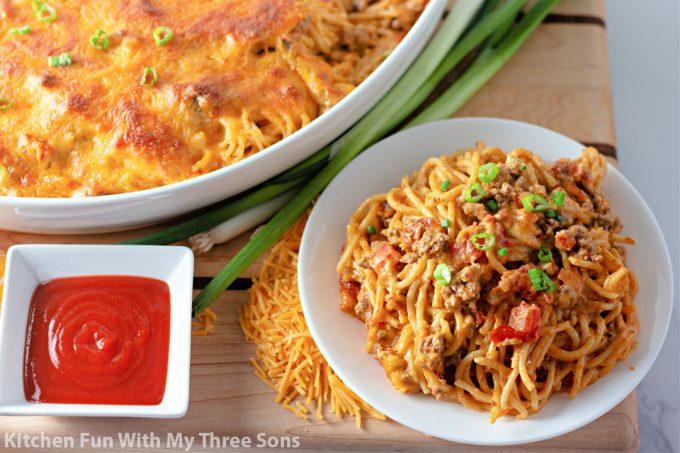 Cheesy Taco Spaghetti with hot sauce and onions