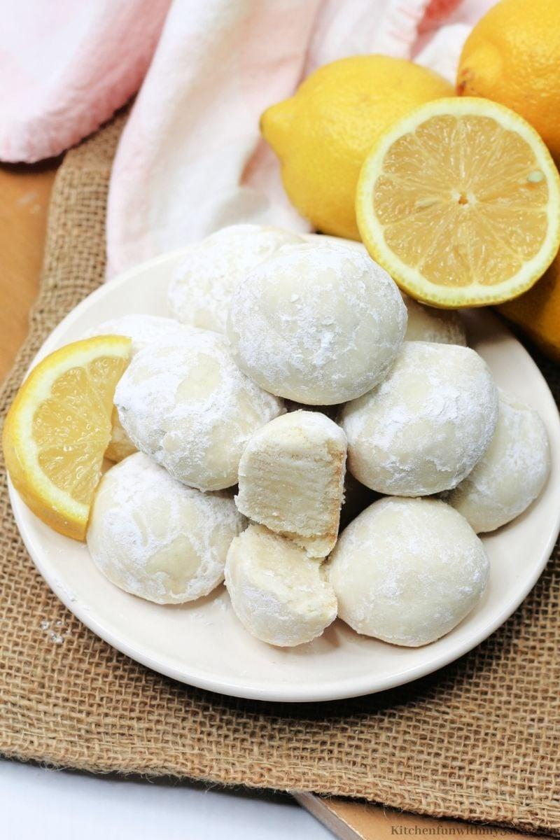 The lemon cookies with extra fresh lemons around it.
