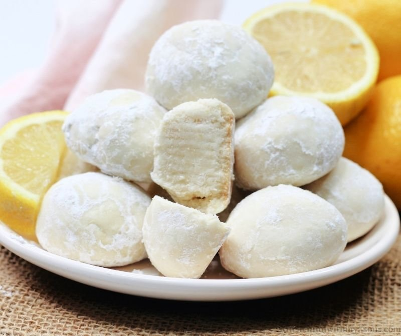 The snowball cookies on a white serving dish.