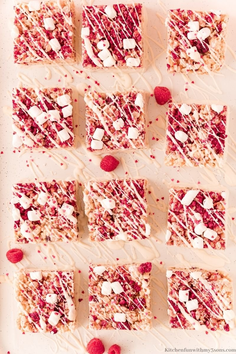 The treats cut into squares with fresh raspberries surrounding them.