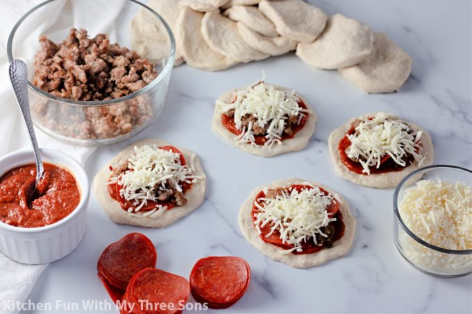 cheese on top of the pizzas.