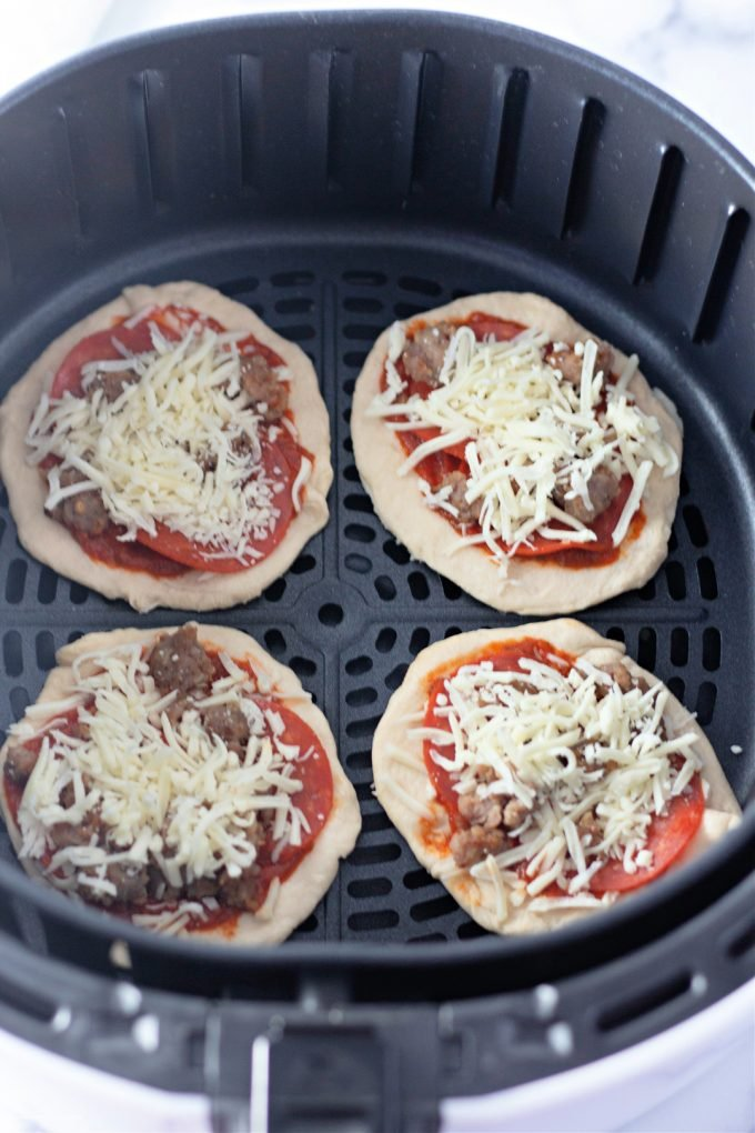 placing the pizzas in the air fryer.
