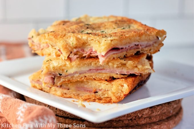 Baked Ham and Cheese Sandwiches on a white plate.