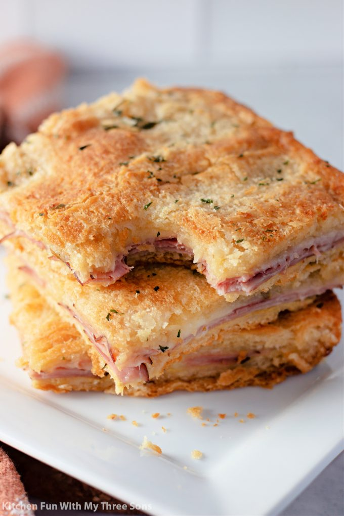 stacked Baked Ham and Cheese Sandwiches with a bite taken out.