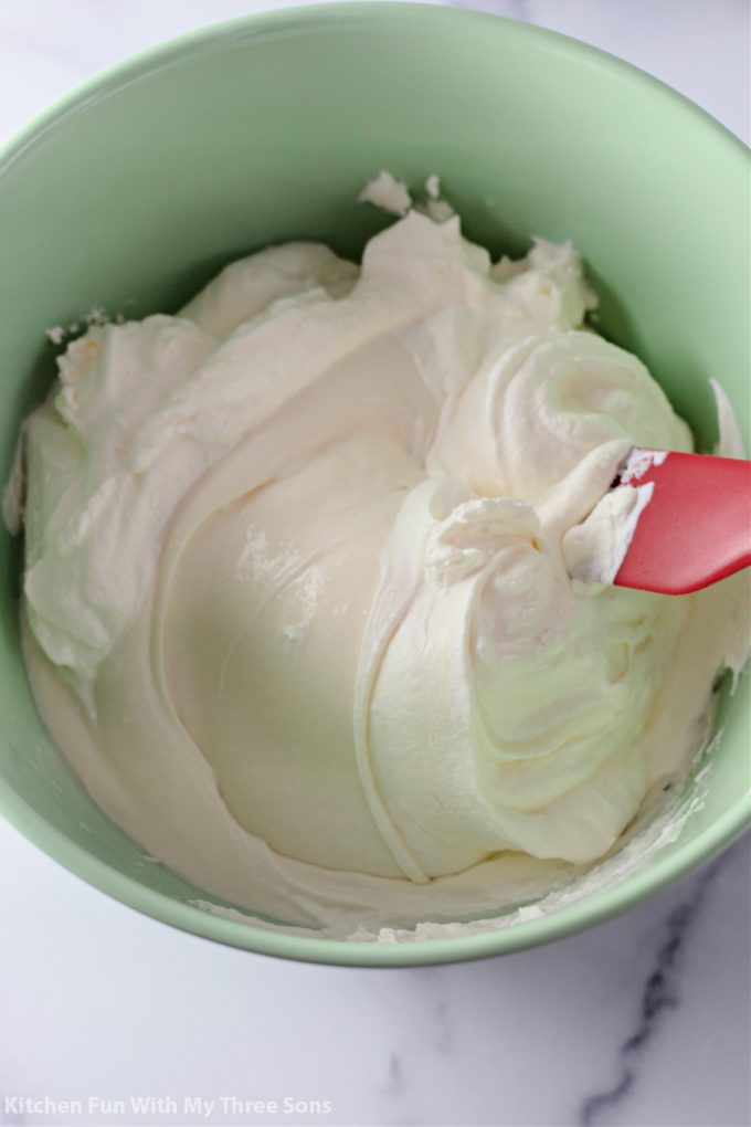 folding the whipped cream in to the cream cheese mixture.