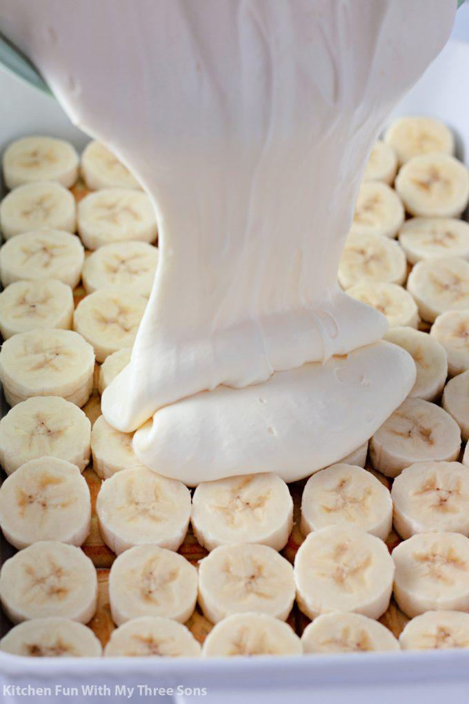 pouring vanilla cream over the bananas.