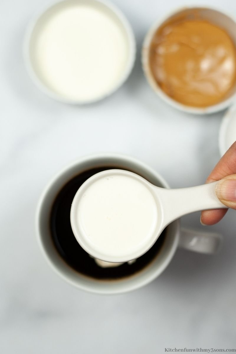 Adding in the heavy cream to the hot coffee.