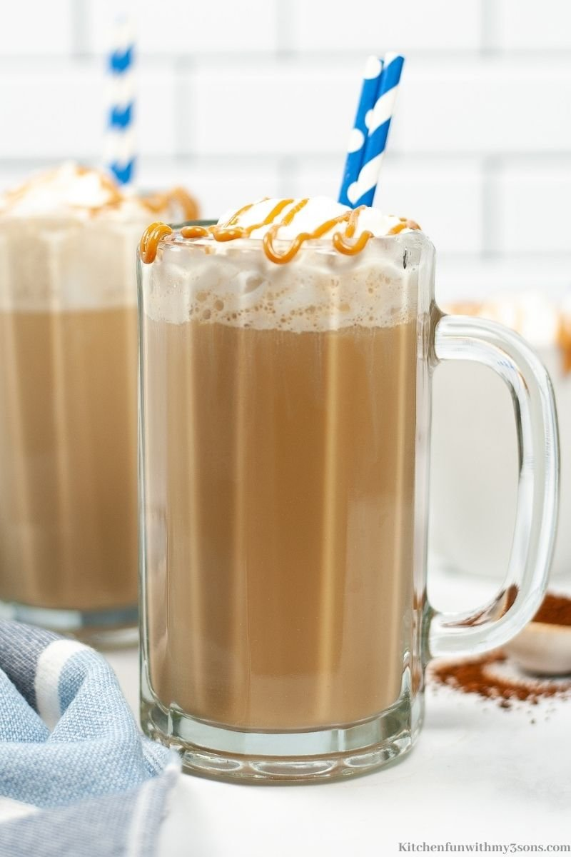 The Copycat Starbucks Macchiato in a tall glass mug with a blue and white striped straw.