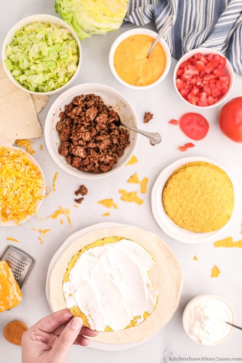 Sour cream spread on to the tostada.
