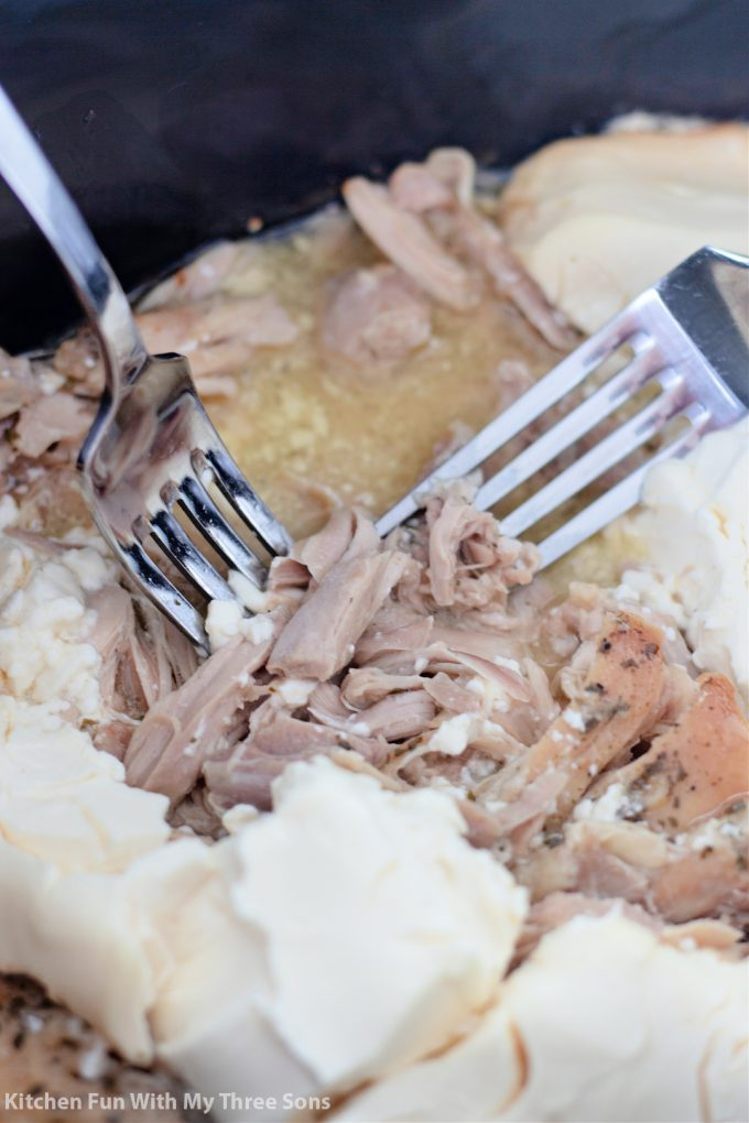 shredding the chicken with two forks.