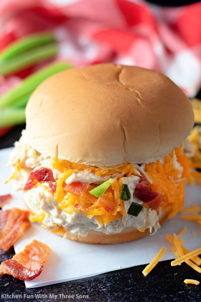 shredded chicken sandwich on a white paper with bacon and cheese.
