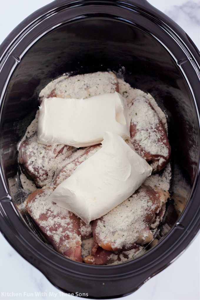 chicken thighs, ranch dressing mix, and cream cheese in a crock pot.