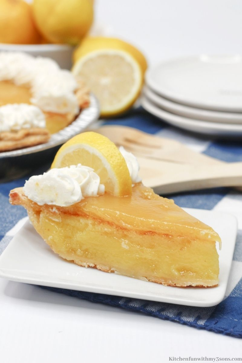 Lemon Chess Pie with a lemon wedge and whipped cream on top.