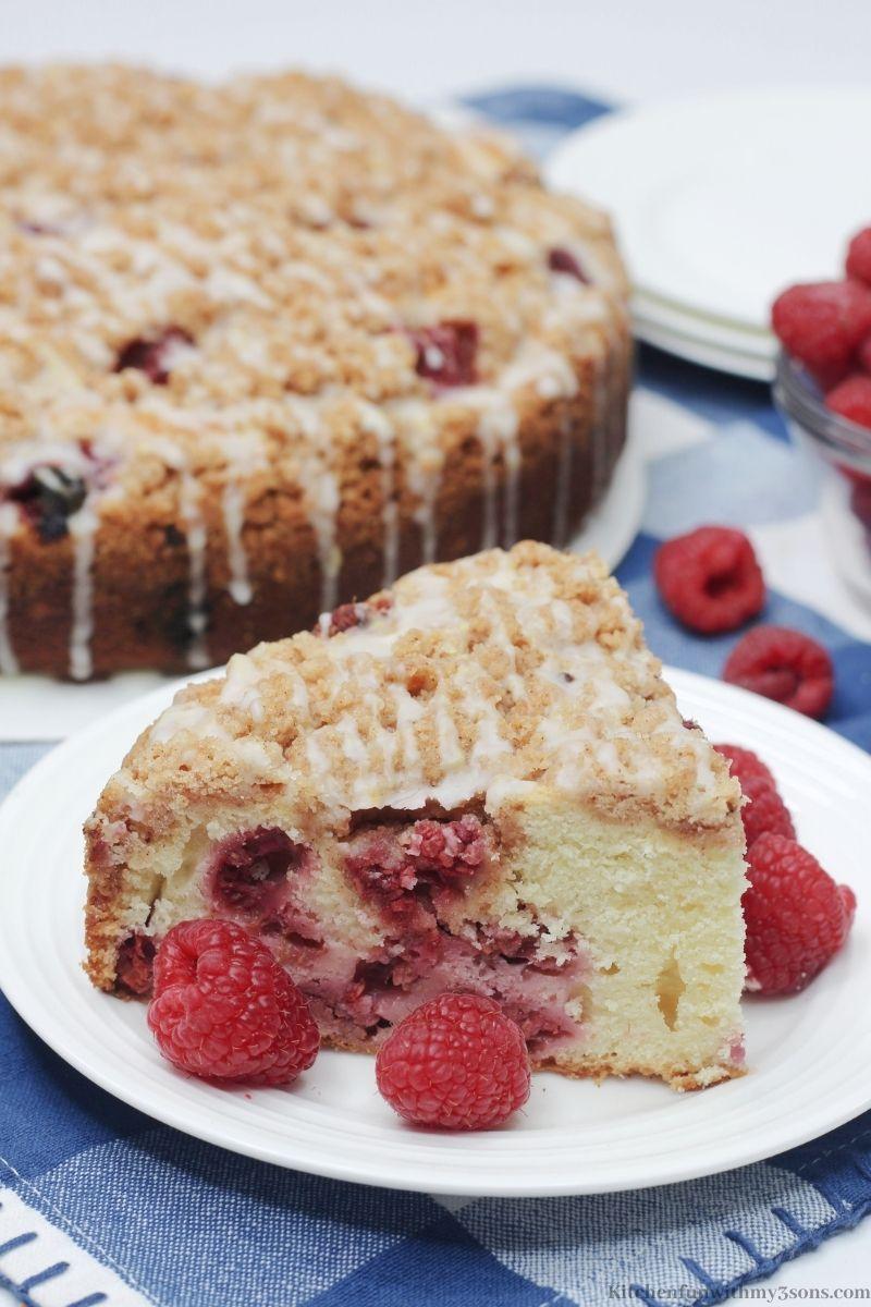 Raspberry Crumble Cake with extra raspberries around it.