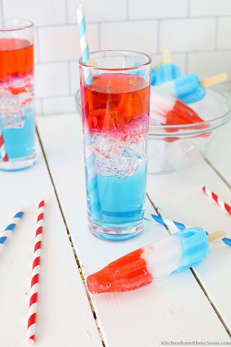 Red White and Blue Cocktail with straws and one popsicle next to it.