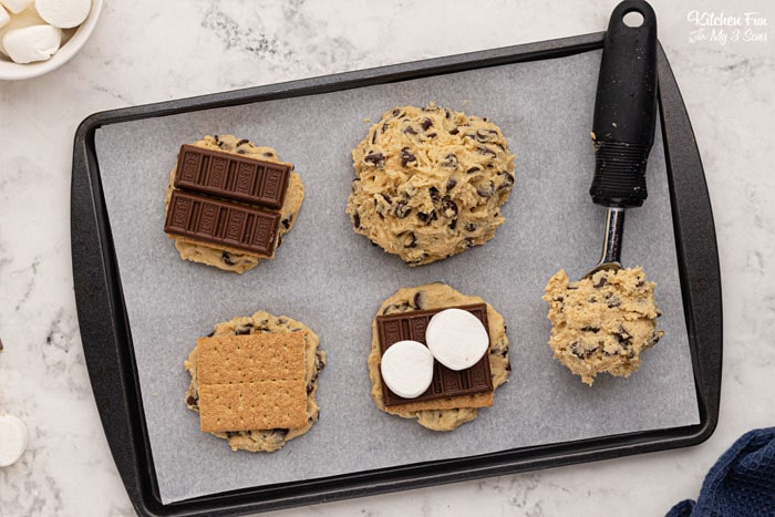 Smores Stuffed Cookies are a sandwich of homemade chocolate chip cookies with graham crackers, marshmallows and Hershey's chocolate stuffed inside.