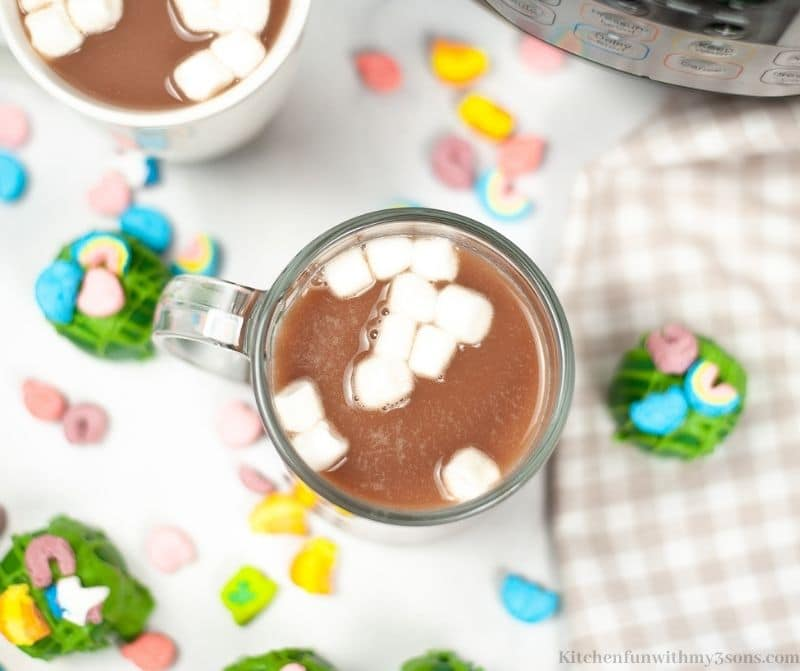 A mug of Hot Cocoa with cocoa bombs around it.