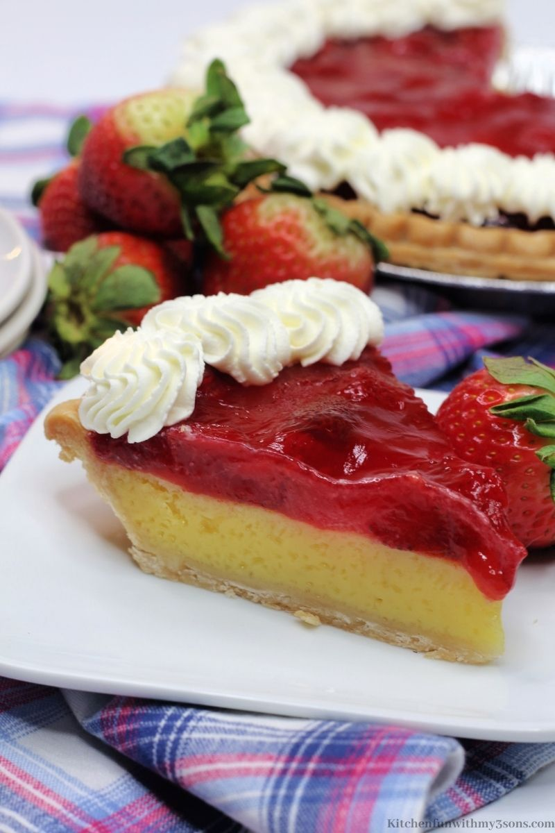 Strawberry Lemon Easy Cheese Pie on a white plate with the rest of the pie behind it.