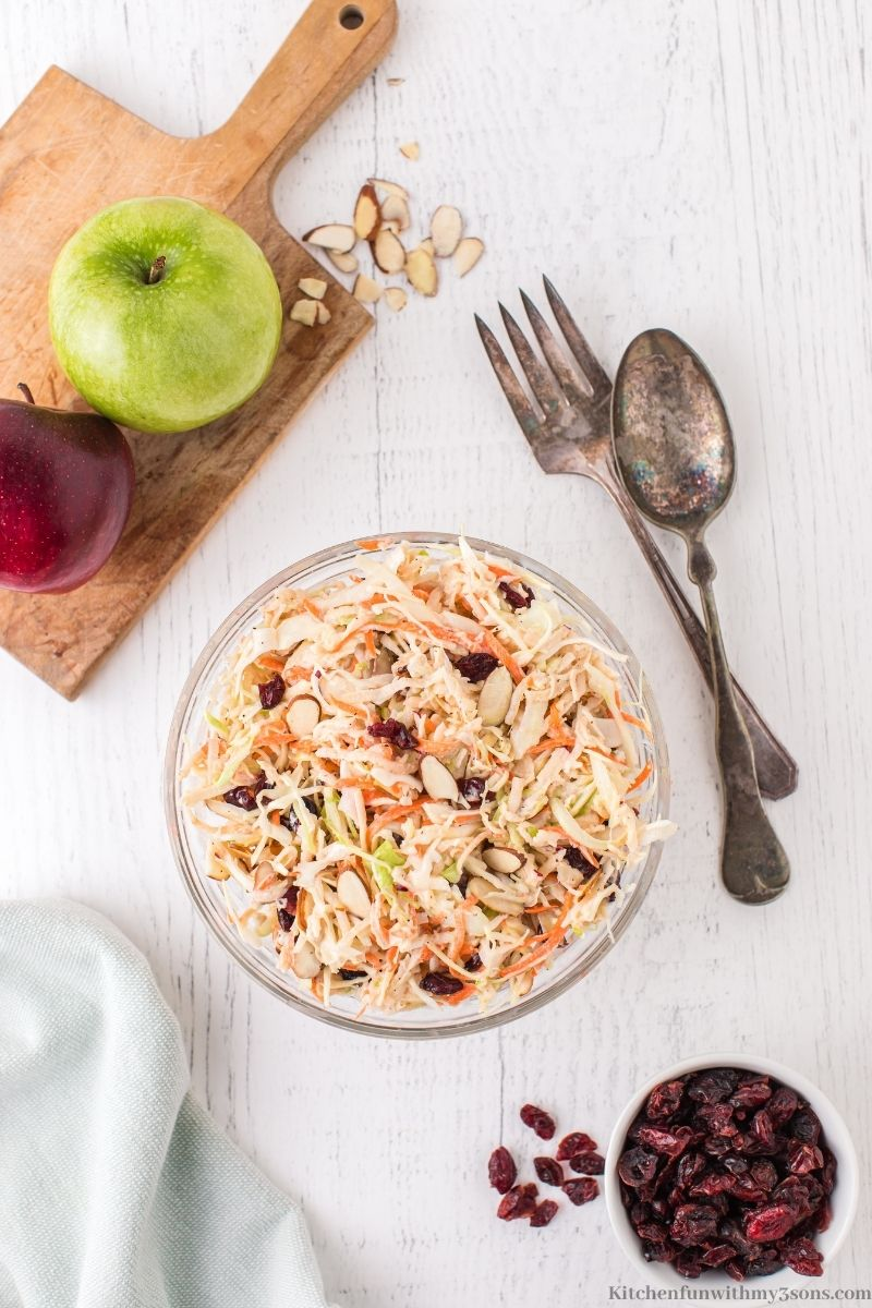 The Apple Slaw in a serving bowl with a fork and spoon next to it.