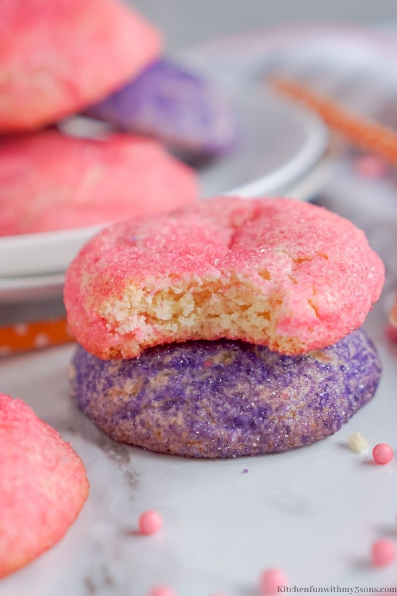 A pink cookie with a bite taken out of it on top of a purple sugar cookie.