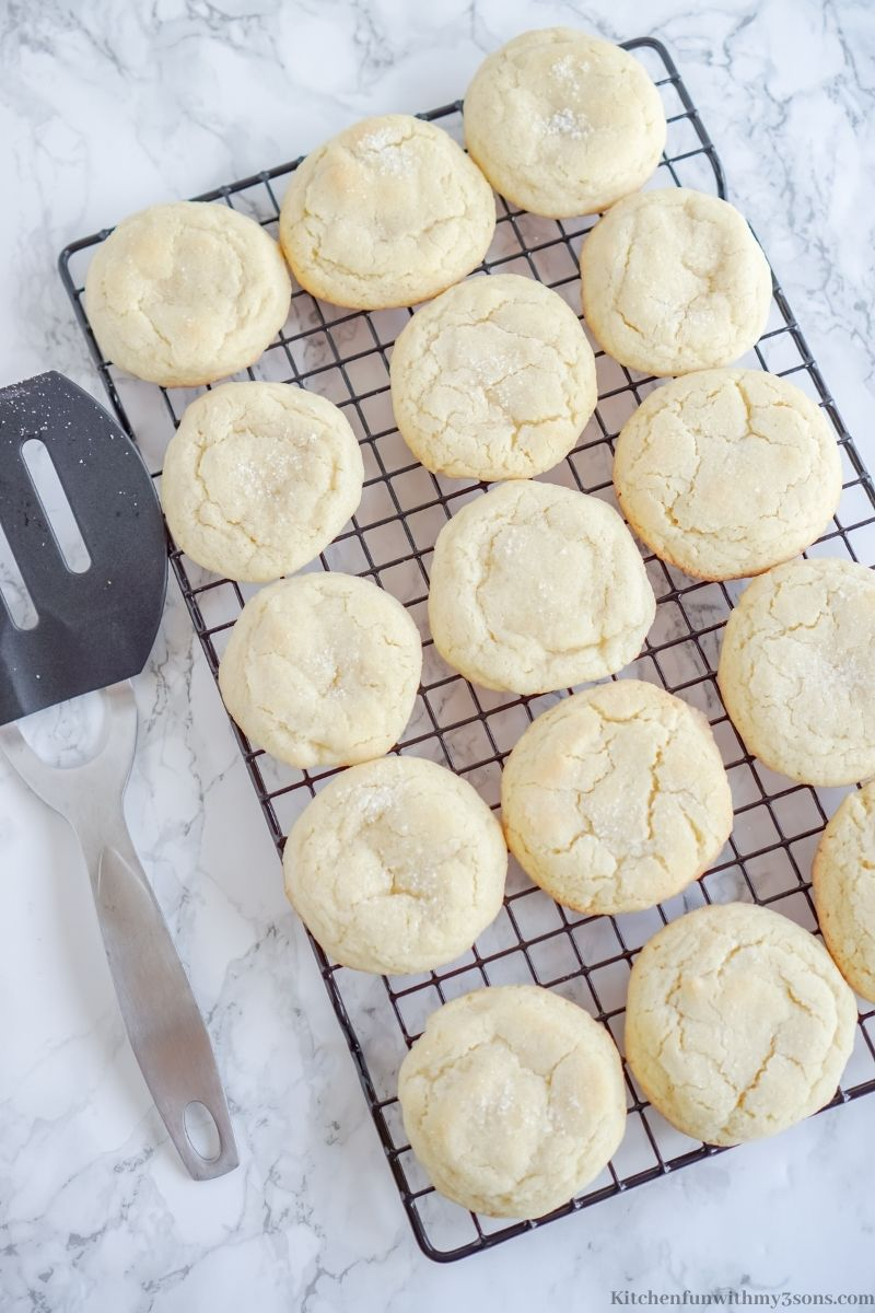 Adding the sugar cookies onto the cooling rack.