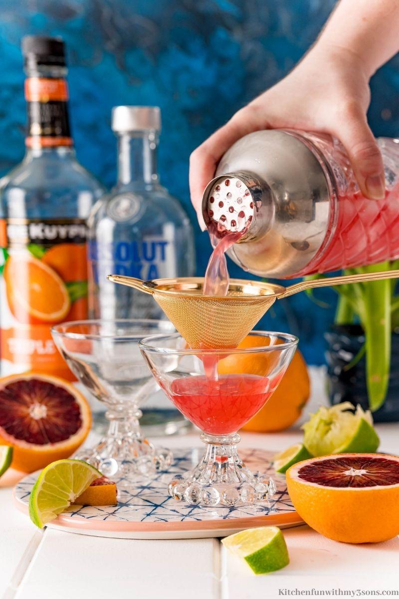 straining the blood orange martini into the prepared martini glass