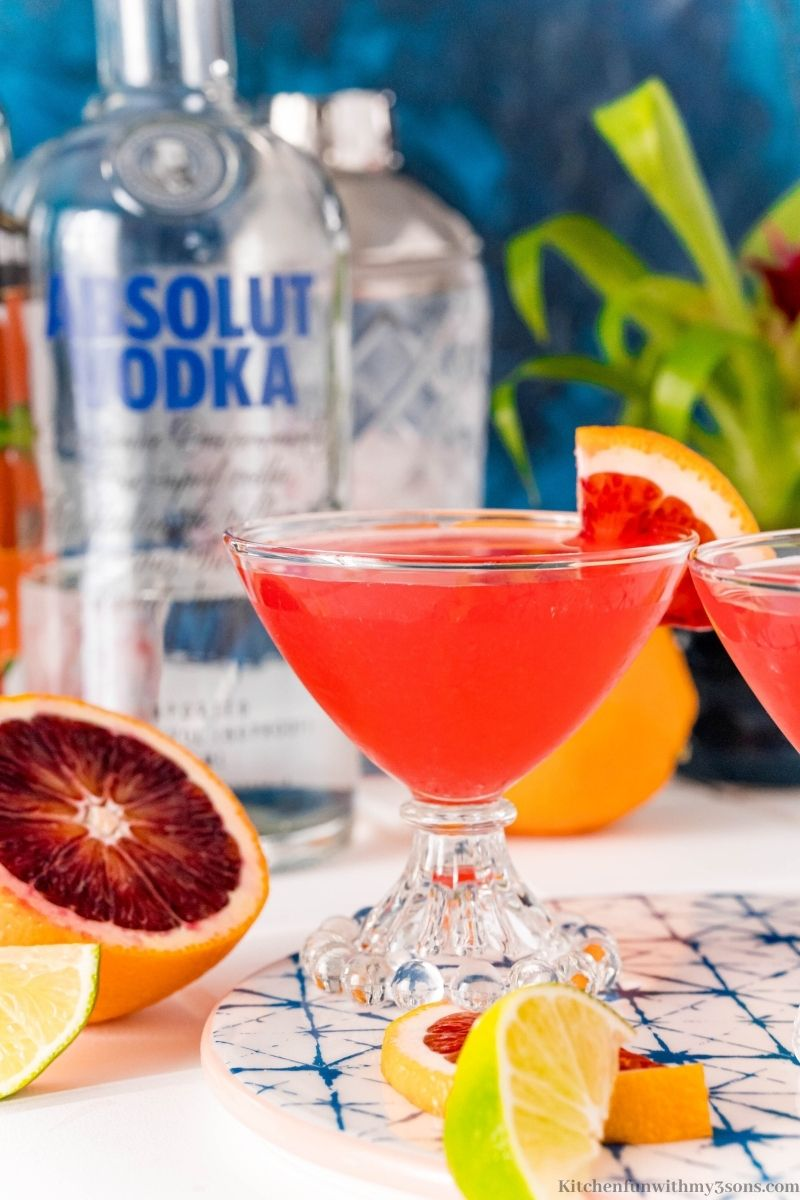 A blood orange martini with a liqueur bottle and cocktail shaker behind it.