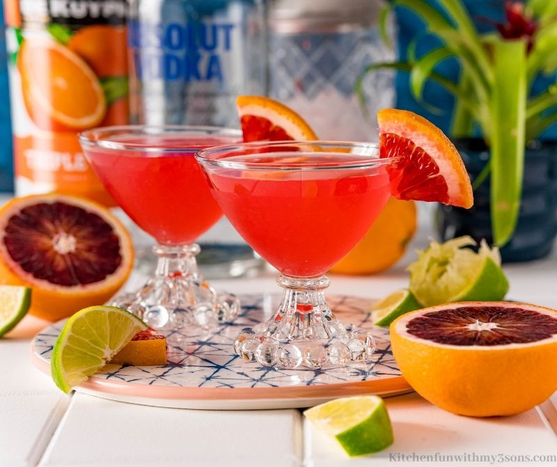 Two cocktails garnished with blood oranges.