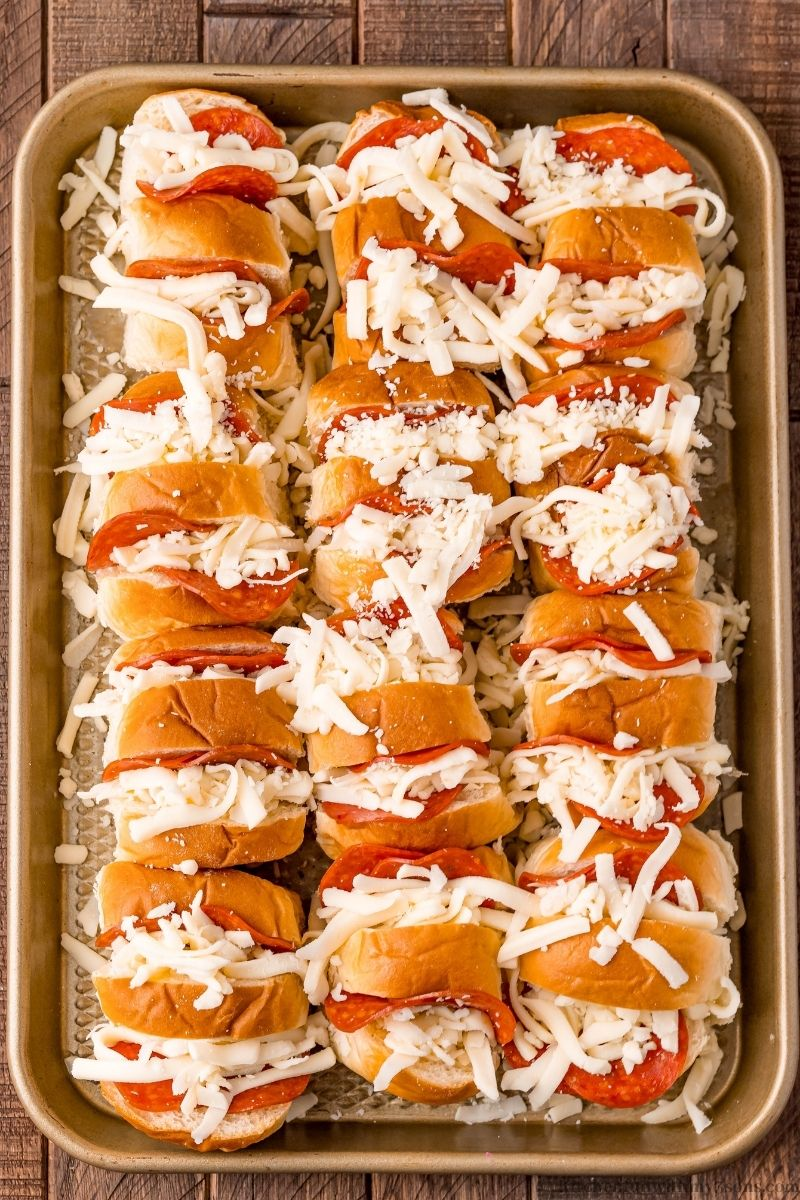 Adding the mozzarella on top of the rolls.