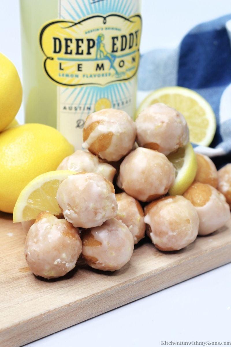 The lemon donuts holes with the lemon liquor behind it.