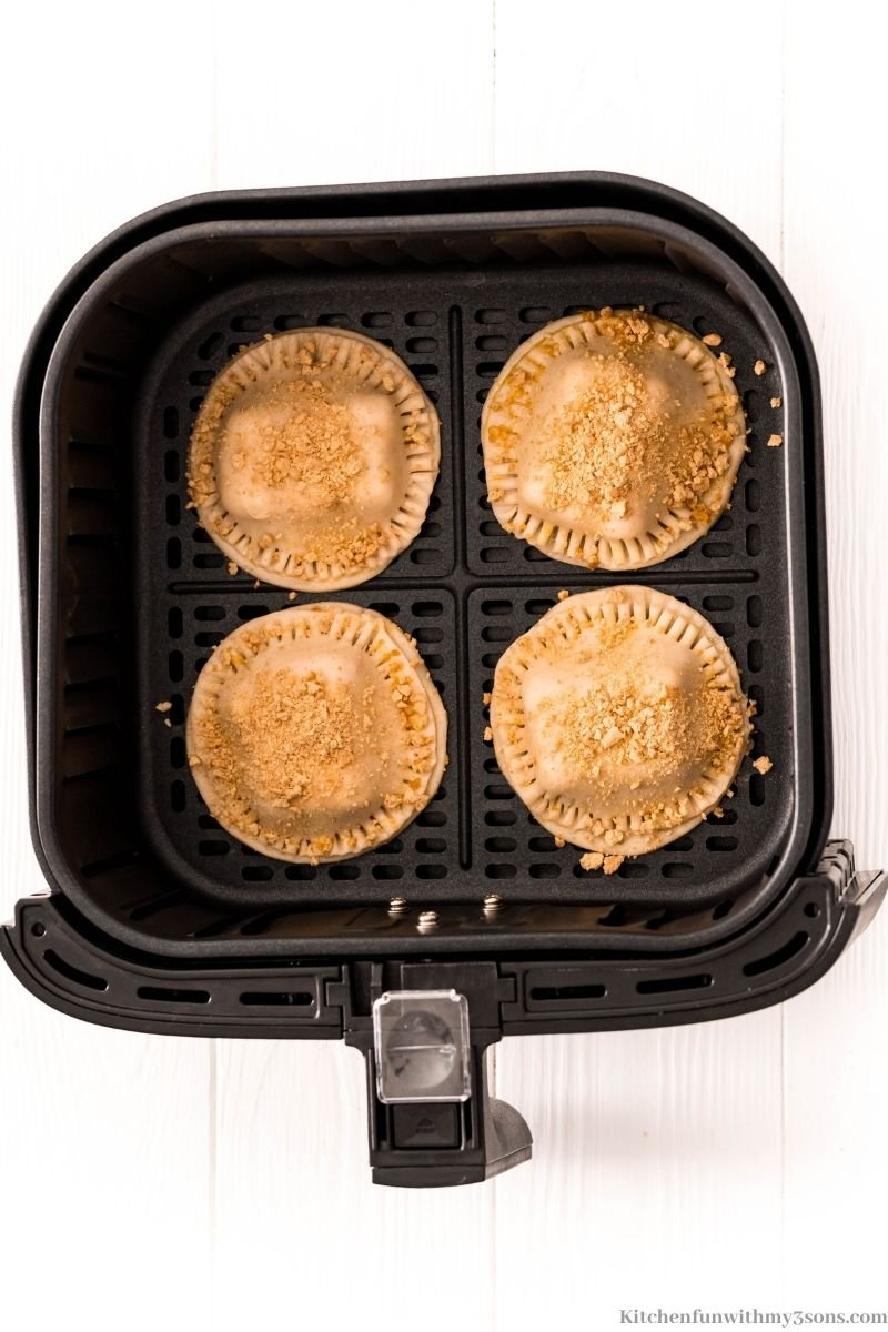 The air fryer smores hand pies topped with graham crackers in the air fryer.