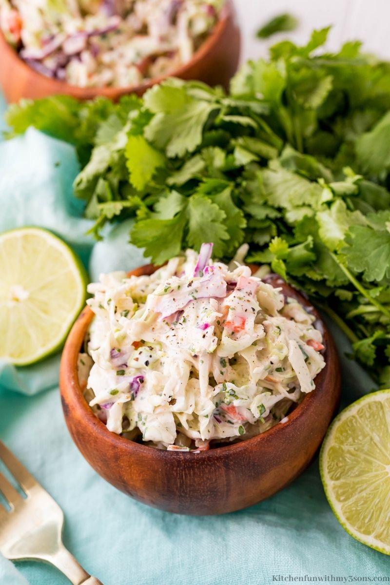 The coleslaw in a small wooden bowl.