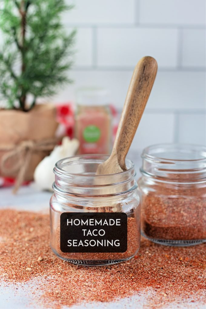 Homemade Taco Seasoning in a glass jar with a wooden spoon.