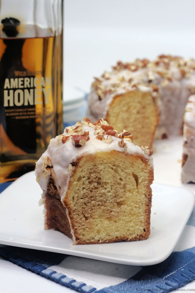 A piece of the Bundt cake with the Whiskey bottle behind it.