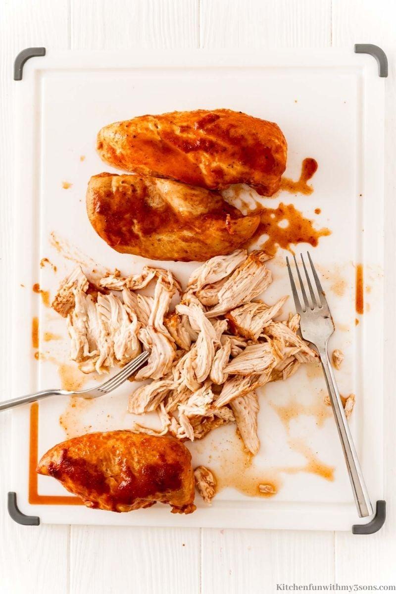 Shredding the chicken on the cutting board.